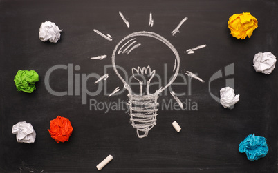 New idea concept with handdrawn lightbulb and crumpled paper