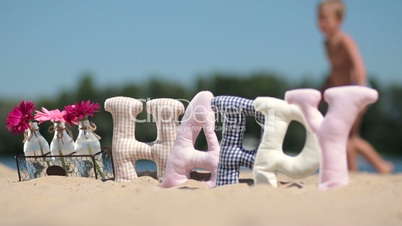 Word happy fabric padded letters on the sand