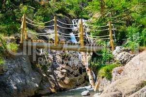 bridge over a mountain river and stony bank