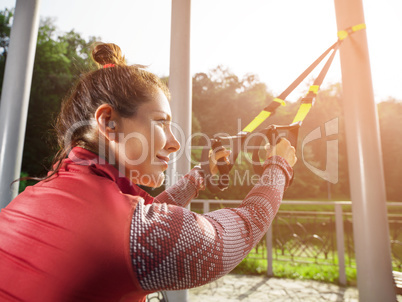 Young beautiful woman doing fitness training with suspension straps.