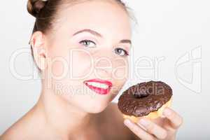 young woman in bright makeup eating a tasty donut with icing. Funny joyful woman with sweets, dessert. dieting concept. junk food. girl licking their fingers