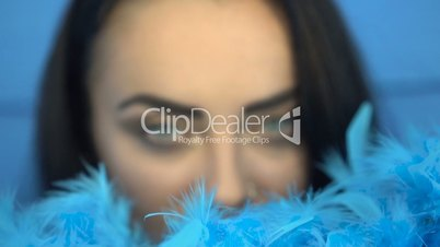 Closeup of beautiful brunette woman smiling and looking into the camera with blue feather boa over blue wall background