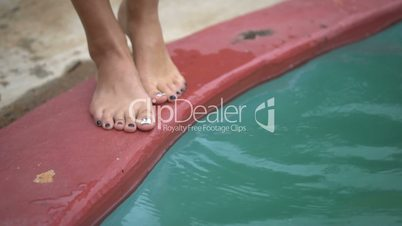 Closeup of woman legs standing on edge of swimming pool and putting feet into water