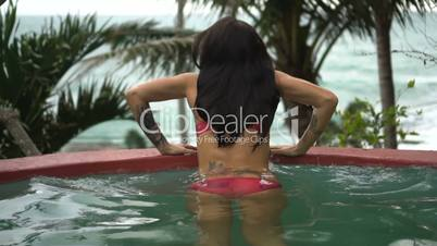 Back view of beautiful sexy brunette woman wearing pink bikini relaxing at the edge of swimming pool at tropical resort