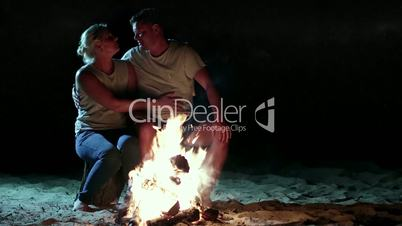 Romantic couple near fire at night while camping