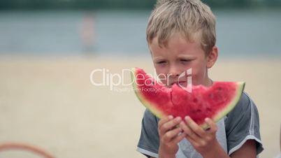 Litttle boy eating delicious watermelon on beach