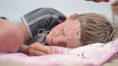 Mother caressing her son asleep