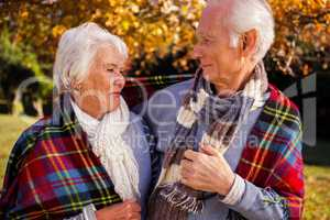 Senior couple embracing with a cover on their shoulder