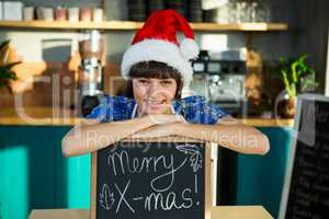 Smiling waitress wearing a santa hat and sitting with a X-mas si