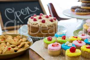 Close-up of various sweet foods on table with open signboard