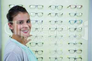 Smiling female customer standing in optical store