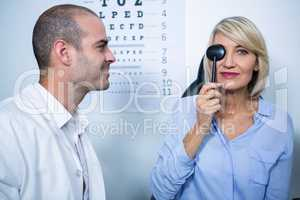 Optometrist examining female patient with medical equipment