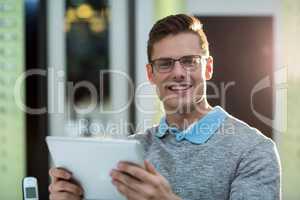Smiling customer using digital tablet in optical store
