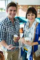 Portrait of smiling couple with coffee cups using a digital tabl