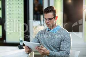 Customer using digital tablet in optical store