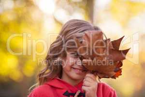 Girl covering face with autumn leaves