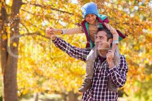 Father carrying son on shoulder against autumn tree