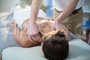 Physiotherapist giving physical therapy to the neck of a female