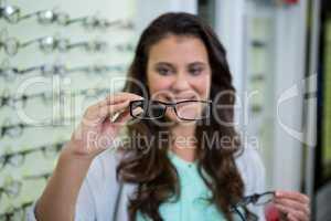 Female customer choosing spectacles in optical store