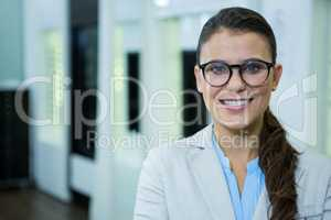 Optometrist in spectacles smiling in optical store