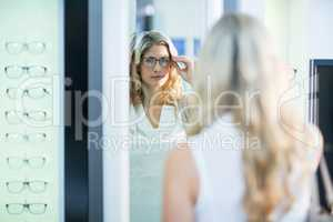 Beautiful female customer trying spectacles