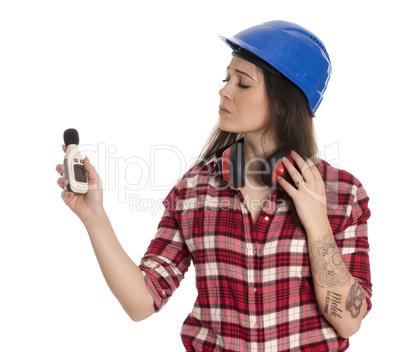 Weiblicher Handwerker hält ein Lärmpegel Meßgerät