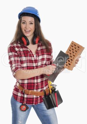 Weiblicher Handwerker hält eine Kelle und Backstein