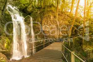 Wooden bridge over a small waterfall in the forest