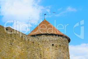 fortress tower with tiled roof on blue sky background