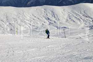 Skier on slope in sun evening