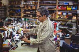 Shoemaker applying glue on shoe