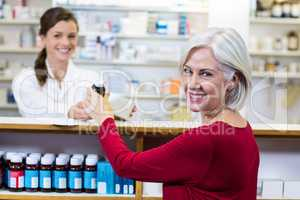 Pharmacist giving medicine to customer in pharmacy