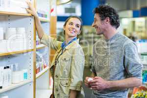 Couple checking a medicine on shelf in pharmacy