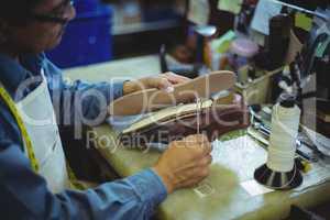 Shoemaker stitching shoe sole with needle