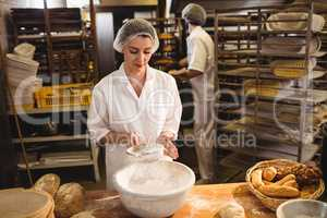 Female baker sifting flour through a sieve
