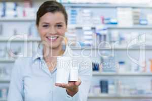 Smiling pharmacist showing medicine container in pharmacy