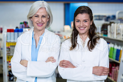 Smiling pharmacists standing with arms crossed in pharmacy