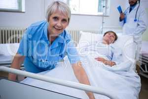 Smiling nurse spreading a blanket over patient