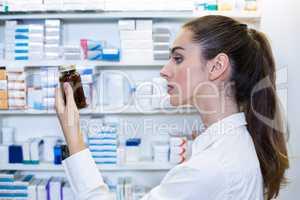 Pharmacist checking a bottle of drug