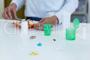Pharmacist putting pill in container at pharmacy