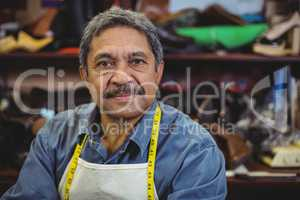 Portrait of shoemaker standing in workshop