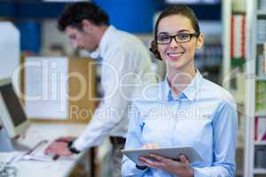 Smiling pharmacist holding digital tablet in pharmacy