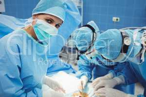 Surgeon looking at camera while colleagues performing operation