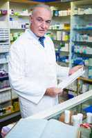 Pharmacist holding a clipboard in pharmacy