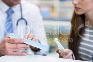 Customer and pharmacist reading pregnancy test