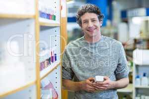 Customer holding a bottle of drug in pharmacy