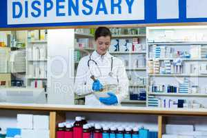 Pharmacist grinding medicine in mortal and pestle at counter
