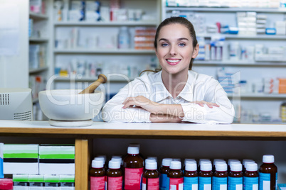 Smiling pharmacist sitting at counter in pharmacy