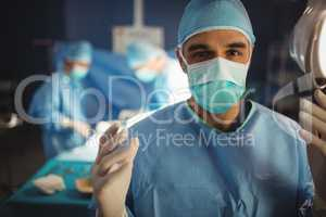 Portrait of male surgeon preparing for operation in operation ro