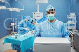 Portrait of surgeon holding ice box while colleagues performing